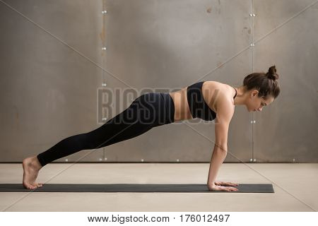 Young attractive yogi woman practicing yoga, standing in Plank exercise, doing Push ups or press ups, phalankasana pose, working out wearing black sportswear, cool urban style grey studio, full length