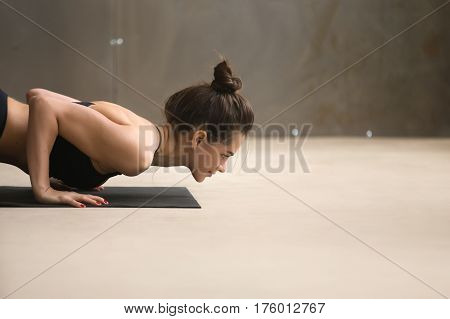 Close up portrait of young woman practicing yoga, doing four limbed staff exercise, Push ups, press ups, chaturanga dandasana pose, working out wearing black sportswear, urban style studio, copy space