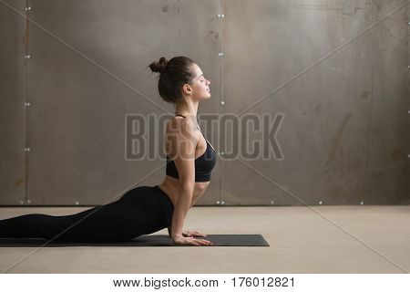Portrait of young attractive yogi woman practicing yoga, doing Urdhva mukha shvanasana exercise, upward facing dog pose, working out wearing black sportswear, cool urban style grey studio, copy space