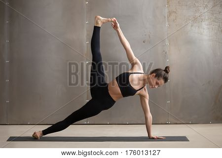 Young attractive yogi woman practicing yoga, standing in Side Plank exercise, Full Version of Vasisthasana pose, working out, wearing black sportswear, urban style, full length, grey studio background