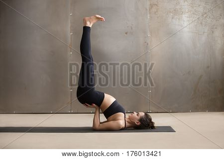 Young attractive yogi woman practicing yoga, stretching in Viparita Karani exercise, working out, wearing black sportswear, cool urban style, full length, grey studio background, side view