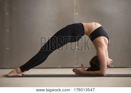 Young attractive yogi woman practicing yoga, stretching in Elbow Bridge exercise, Dvi Pada Viparita Dandasana pose, working out, wearing black sportswear, cool urban style, full length, grey studio