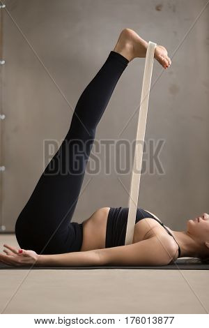 Woman in black practicing yoga, stretching in Double Leg Lift, Urdhva Prasarita Padasana exercise using strap, Upward Extended Feet pose, working out, cool urban style, grey studio midsection close up