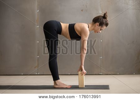Young attractive yogi woman practicing yoga, standing in head to knees, Ardha uttanasana exercise, using block, Standing Half forward bend pose, working out, cool urban style, full length, grey studio