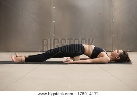 Young attractive sporty yogi woman practicing yoga, stretching in dvi pada pithasana exercise using wooden block, working out, wearing black sportswear, cool urban style, full length, grey studio