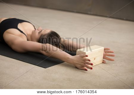 Young attractive yogi woman practicing iyengar yoga using wooden block, lying on the floor, working out, wearing black sportswear, cool urban style, grey studio background, closeup