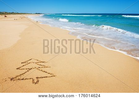 Drawing of Christmas tree on the beach sand - Christmas holiday vacation and travel concept