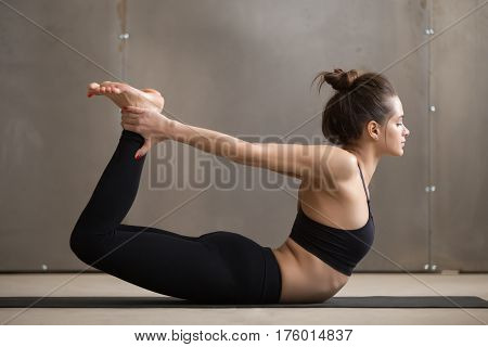 Young attractive yogi woman practicing yoga, stretching in Dhanurasana exercise, Bow pose, working out, wearing black sportswear, cool urban style, full length, grey studio background, side view