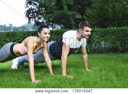 Young happpy couple exercising and stretching muscles before sport activity