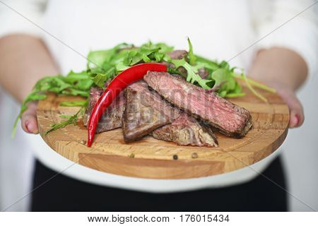 Sliced medium rare grilled Beef steak Ribeye with rocket salad in hands of a woman