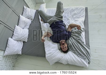 Furious man is frantically crying. He lying across bedstead and making fists. Top view