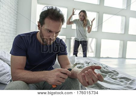Insanity in family. Serious man is holding paper-cutter near his hand and looking at it with depression. His wife is screeming