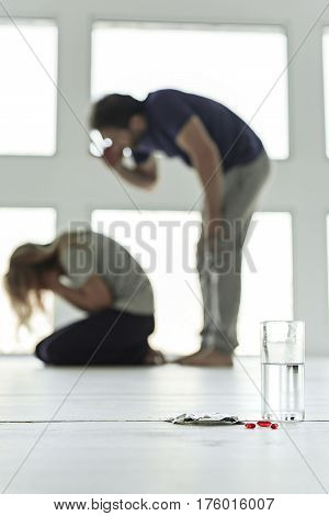 Focus on capsules beside glass with water on floor. Quarrel between husband and wife on background