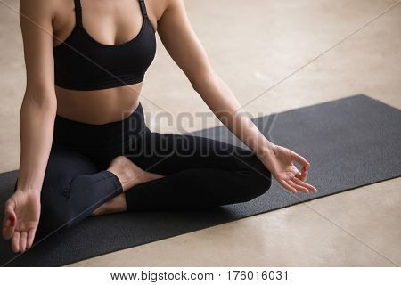 Young sporty yogi woman practicing yoga, sitting in Sukhasana exercise, Easy Seat pose with mudra, working out, wearing black sportswear, urban style grey studio floor background, midsection closeup