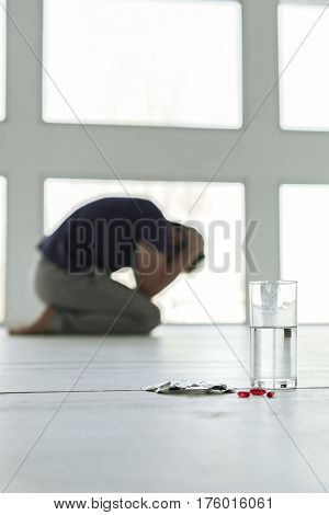 Despaired man is kneeling on floor. Focus on small red pills near glass of water