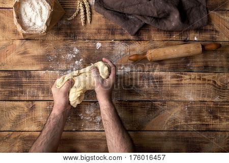 Male hands knead the dough on a wooden table top view