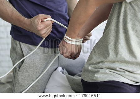 Domestic troubles. Cruel husband binding hands of his wife behind her back by rope. Close up