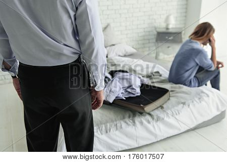 Upset woman is sitting on bed near open bag with clothes. Man standing in room