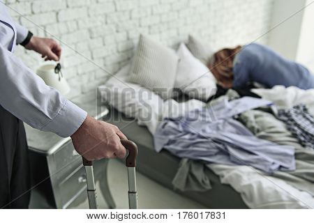Male person holding clef. Offended woman is lying on disassembled bed