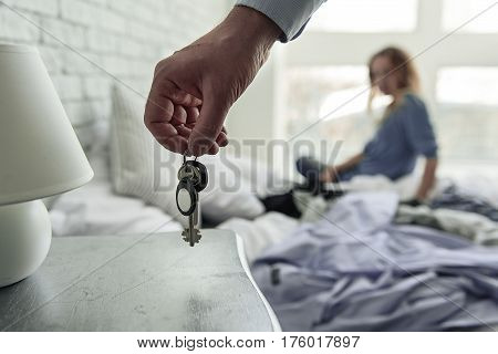Sad woman is sitting on bed. Male person keeping keys above nightstand. Close up
