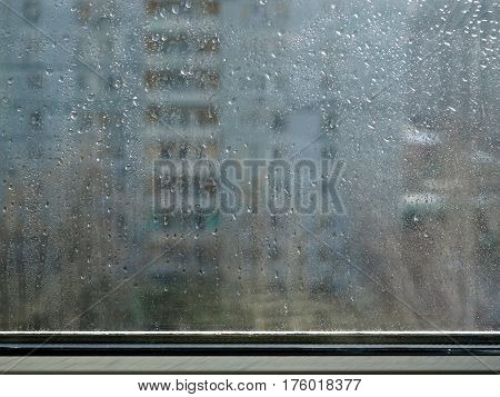Rain in the city. Drops on glass window