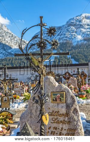 SAPPADA, ITALY - FEBRUARY 20, 2017: Wrought crucifix on tombstone on the catholic cemetery on a sunny winter day.