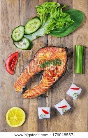 Grilled salmon with vegetables and rice on wooden plate. Top view