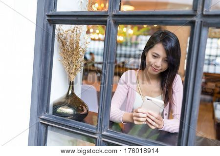 Window though woman use of mobile phone in restaurant