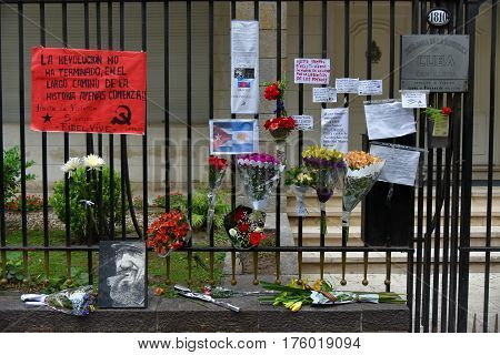 Buenos Aires Argentina - Nov 26 2016: Flowers and signs on a fence at the Embassy of Cuba in Buenos Aires Argentina.