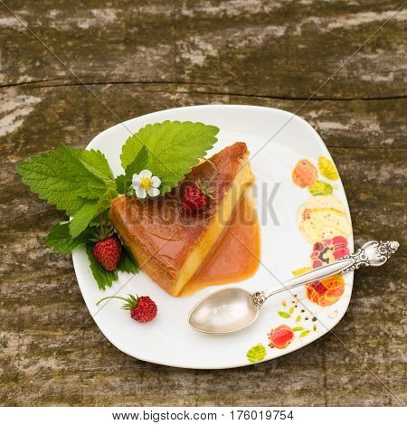 Delicious homemade Flan dessert or creme caramel dessert with mint. Slice of Milk Pudding over a wooden table. Brazilian Flan with strawberries. Panna cotta dessert with caramel sauce.