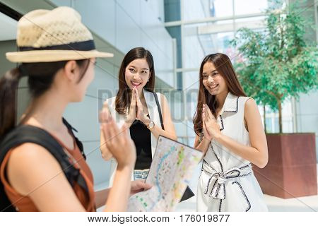 Woman traveler holding city map and say good bye to the local people in Bangko city