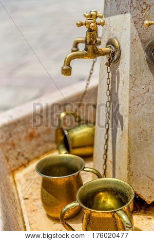 Public golden mugs for ritual of hand washing at the Western Wall located in the old city Jerusalem at the foot of the western side of the Temple Mount, Israel.