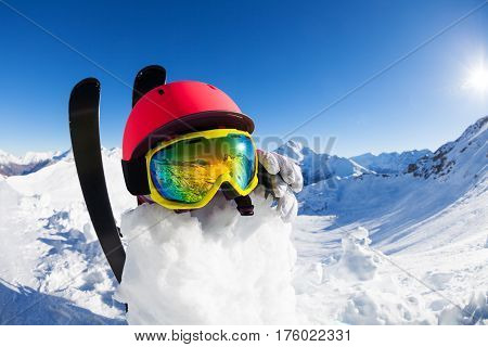 Funny snowman wearing safety helmet, ski mask and gloves against the blue sunny sky