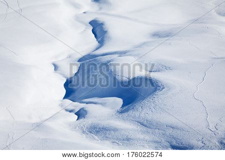 Top view picture of winter snowcapped mountains hill cowered with curving ski or snowboarding traces