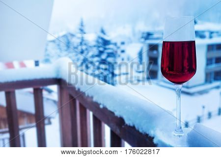 A glass of cold red wine on the snow-cowered balcony balustrade of hotel suite