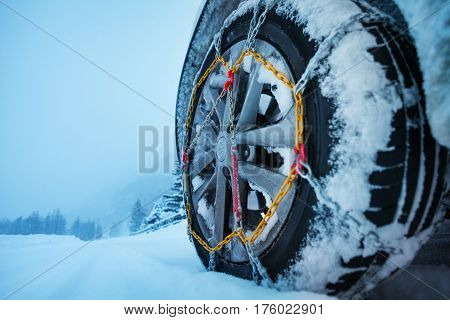 Close-up picture of automobile wheel with ice chains for tires on the snow-covered road