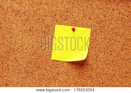 Yellow sticky notes with pin on a cork board