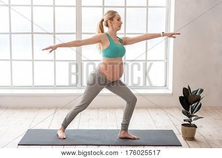 Staying healthy for her baby. Full length portrait of beautiful happy expectant female enjoying stretching while standing at home