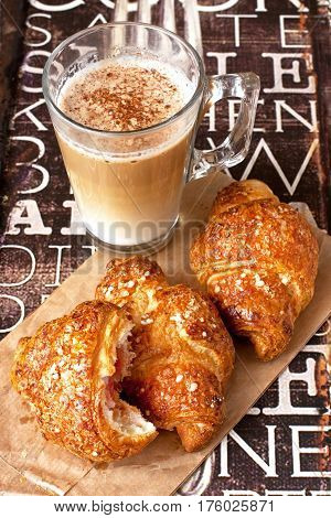 Fresh croissants  and coffee cup for breakfast on wooden  vintage table