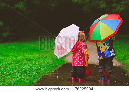 little boy and girl with umbrellas playing in spring nature