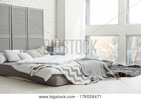 Luxury and coziness. Comfortable big bed in house. Light pastel ton colors and large window create domestic atmosphere