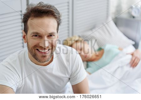 I am so happy. Waist up portrait of middle aged man looking at camera and laughing. He is sitting on bed while woman napping peacefully