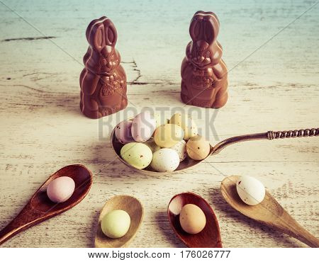 Easter Sugar Coated Candy Eggs On Wooden And Silver Spoons With Chocolate Bunnies On White Wooden Ba