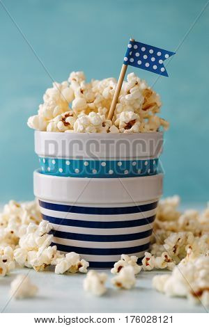 Homemade buttered popcorn served in bowls decorated with party flag.