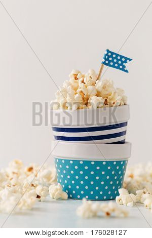 Homemade buttered popcorn served in colorful bowls decorated with party flags.