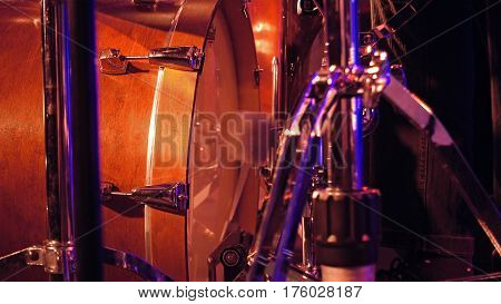 Drummer plays on a bass drum set with pedal on the stage. Jazz or rock concert performance entertainment. Close up shot with soft selective focus.