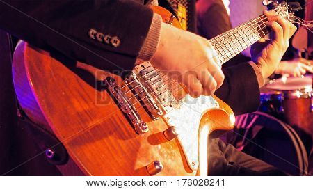 Guitar player plays the electric guitar on the stage. Jazz or rock concert performance entertainment. Close up shot with selective focus.