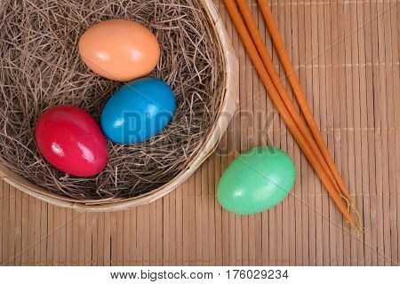 Multicolored eggs in the straw in a basket and candles on a mat next