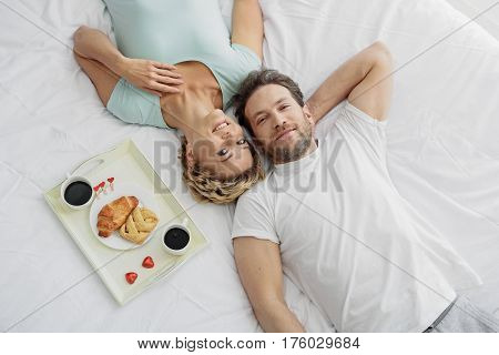 Top view of carefree man and woman relaxing on bedding together. They are looking at camera and smiling. Gray with cups of coffee and croissant is also on sheet