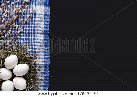 Easter mockup. White eggs unpainted in hay nest, pattern for your colors, on napkin at black background decorated with pussy willow spring flowers. Top view with copy space
